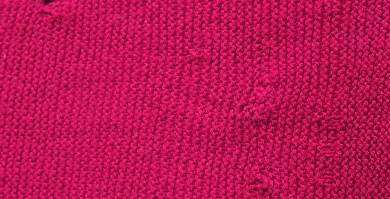 roter schal, unregelmäßig gestrickt, rand läuft schief zu, maschen haben knoten, knubbel und löcher